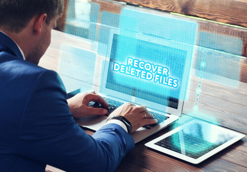 Business, technology, internet and networking concept. Young businessman working on his laptop in the office, select the icon Recover deleted files on the virtual display.