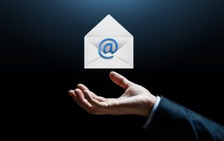 business, online communication and people concept - close up of businessman hand with e-mail message icon over dark background