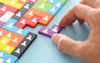 image of tangram puzzle blocks with people icons over wooden table ,human resources and management concept