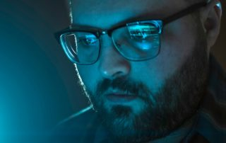 Serious man with reflection of laptop screen with website data in glasses working late, close up. Information analytic or internet marketing or coder developer portrait in blue tones